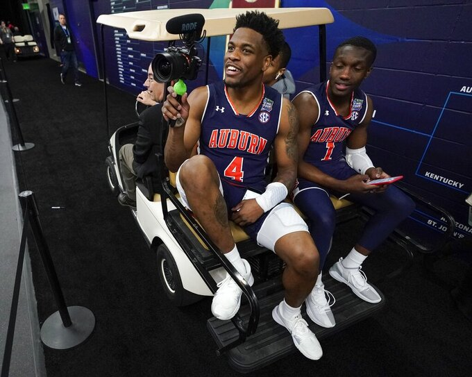 Auburn's Malik Dunbar and Jared Harper get a ride in a gold cart after a practice session for the semifinals of the Final Four NCAA college basketball tournament, Thursday, April 4, 2019, in Minneapolis. (AP Photo/David J. Phillip)