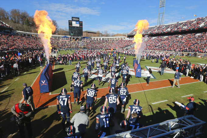The Virginia team runs onto the field before an NCAA college football game against Virginia Tech in Charlottesville, Va., Friday, Nov. 29, 2019. Virginia won the game 39-30. (AP Photo/Steve Helber)