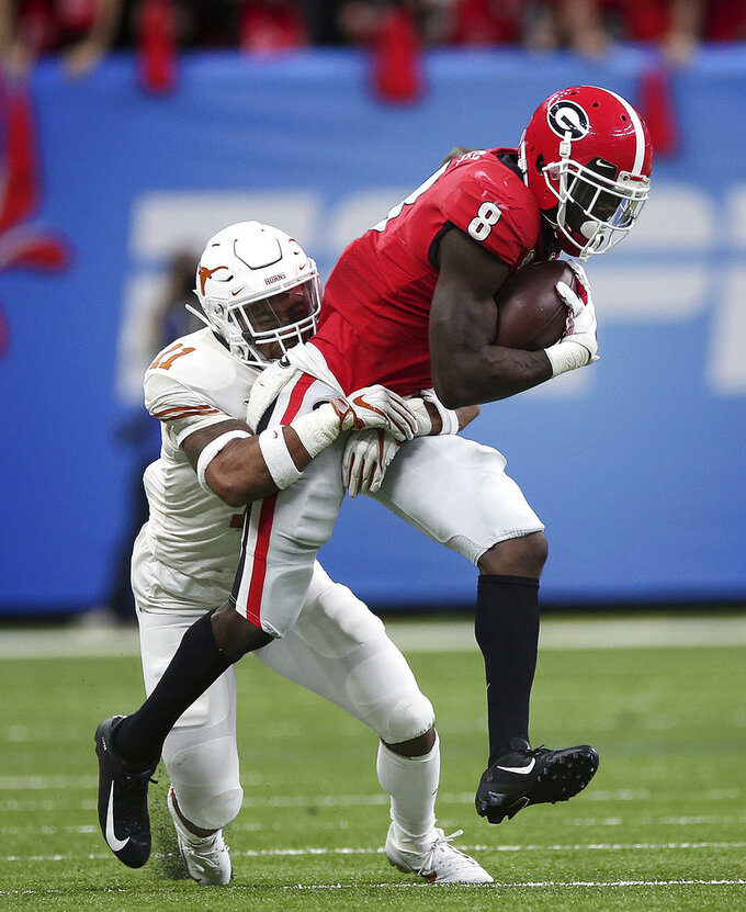 Georgia wide receiver Riley Ridley (8) carries against Texas defensive back P.J. Locke III (11) during the first half of the Sugar Bowl NCAA college football game in New Orleans, Tuesday, Jan. 1, 2019. (AP Photo/Rusty Costanza)