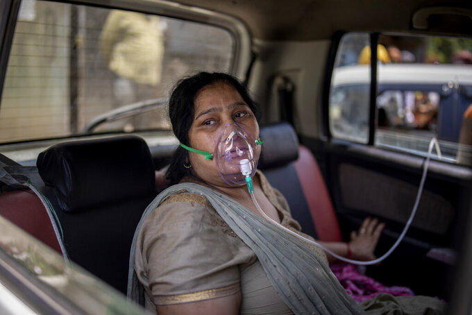 FILE - In this April 24, 2021, file photo, a COVID-19 patient sits in a car and breathes with the help of oxygen provided by a Gurdwara, a Sikh house of worship, in New Delhi, India. Despite clear signs that India was being swamped by another surge of coronavirus infections, Prime Minister Narendra Modi refused to cancel campaign rallies, a major Hindu festival and cricket matches with spectators. The crisis has badly dented Modi's carefully cultivated image as an able technocrat.  (AP Photo/Altaf Qadri, File)