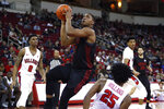 San Diego State's Matt Mitchell drives to the basket next to Fresno State's Anthony Holland, right, during the first half of an NCAA college basketball game in Fresno, Calif., Tuesday Jan. 14, 2020. (AP Photo/Gary Kazanjian)