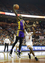 LSU forward Emmitt Williams (5) shoots over Texas guard Matt Coleman III (2) during the first half of an NCAA college basketball game, Saturday, Jan. 25, 2020, in Austin, Texas. (AP Photo/Eric Gay)