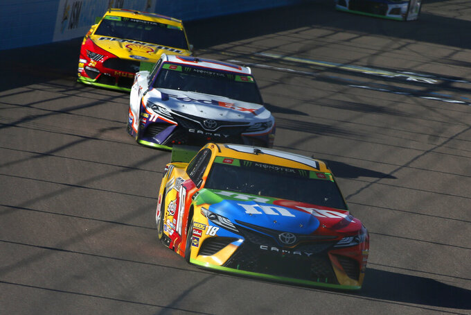 Kyle Busch (18) leads Denny Hamlin (11) and Joey Logano (22) into Turn 1 during a NASCAR Cup Series auto race at ISM Raceway, Sunday, Nov. 10, 2019, in Avondale, Ariz. (AP Photo/Ralph Freso)