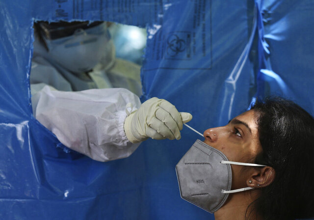 A woman gets her nasal swab sample taken for COVID-19 test at a government health center in Hyderabad, India, Monday, July 27, 2020. India is the third hardest-hit country by the pandemic in the world after the United States and Brazil. (AP Photo/Mahesh Kumar A.)