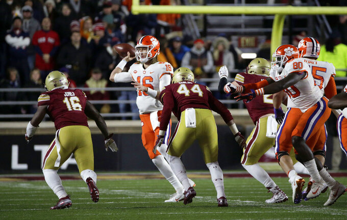 Boston College linebacker Davon Jones (16) and defensive lineman Brandon Barlow (44) put pressure on Clemson quarterback Trevor Lawrence (16) during the first half of an NCAA college football game, Saturday, Nov. 10, 2018, in Boston. (AP Photo/Elise Amendola)