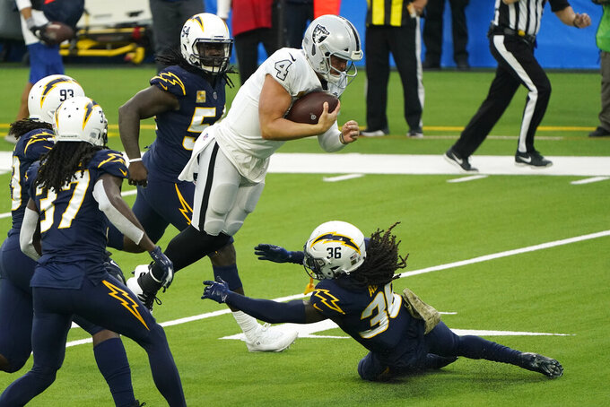 Las Vegas Raiders quarterback Derek Carr leaps over Los Angeles Chargers strong safety Jahleel Addae for a first down during the second half of an NFL football game Sunday, Nov. 8, 2020, in Inglewood, Calif. (AP Photo/Alex Gallardo)
