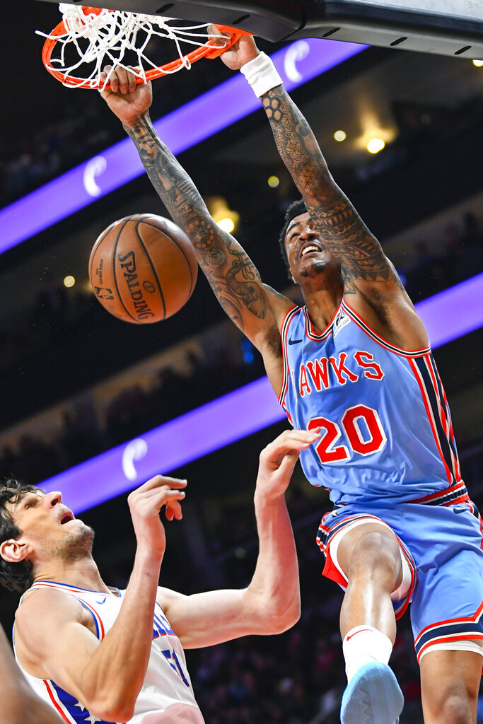 FILE - In this April 3, 2019, file photo, Atlanta Hawks forward John Collins (20) dunks on Philadelphia 76ers center Boban Marjanovic during the first half of an NBA basketball game, in Atlanta. With a pair of picks in the top 10 — or perhaps a single selection that's higher than what they have now, should they work out a trade — the Hawks can add to a pair of gems from the last two NBA drafts, Trae Young and John Collins. (AP Photo/John Amis, File)
