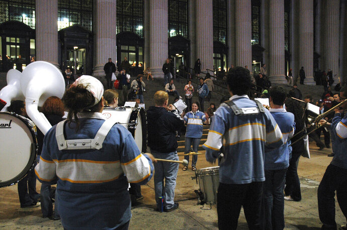 FILE - In this April 15, 2008, file photo, the Columbia University marching band entertains tax filers and others outside the James A. Farley Main Post Office in New York. The band has decided to voluntarily shut itself down over what it called a history