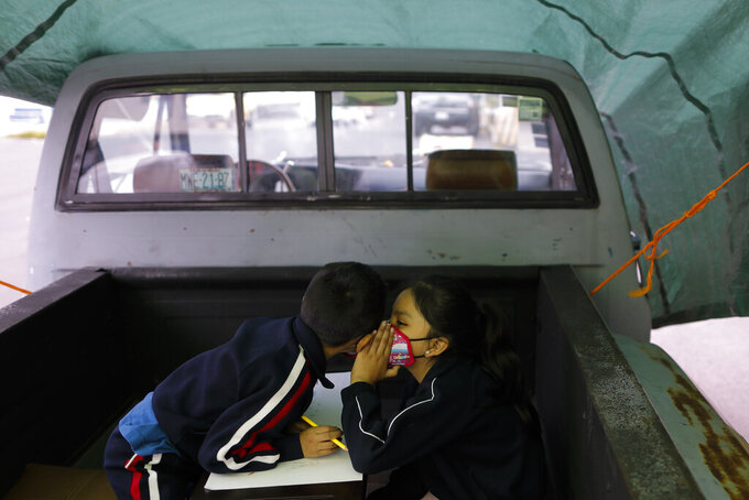 """Paulina Mariano Ortiz, 7, whispers to her brother Axel, 5, in a pick-up truck bed repurposed as an educational space on the southern edge of Mexico City, Friday, Sept. 4, 2020. Concerned about the educational difficulties facing school-age children during the coronavirus pandemic, a couple who runs """"Tortillerias La Abuela,"""" or Grandma's Tortilla Shop, adapted several spaces outside their locale to provide instruction and digital access to neighborhood children who don't have internet or TV service at home, a project which has attracted donations and a waiting list of students. (AP Photo/Rebecca Blackwell)"""