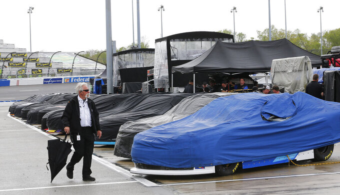Xfinity Series cars sit under tarps as they await qualifying for the evening's race as rain falls in the area at Richmond International Raceway in Richmond, Va., Friday, April 12, 2019. (AP Photo/Steve Helber)