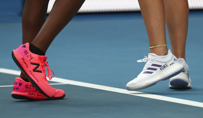 United States' Coco Gauff, left, and compatriot Caty McNally wear a tribute to Kobe Bryant on their shoes during their doubles match against Japan's Shuko Aoyama amd Ena Shibahara at the Australian Open tennis championship in Melbourne, Australia, Monday, Jan. 27, 2020. (AP Photo/Dita Alangkara)