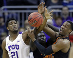 TCU's Kevin Samuel (21) competes for a rebound against Oklahoma State's Cameron McGriff, right, and Yor Anei during the first half of an NCAA college basketball game in the Big 12 men's tournament Wednesday, March 13, 2019, in Kansas City, Mo. (AP Photo/Charlie Riedel)