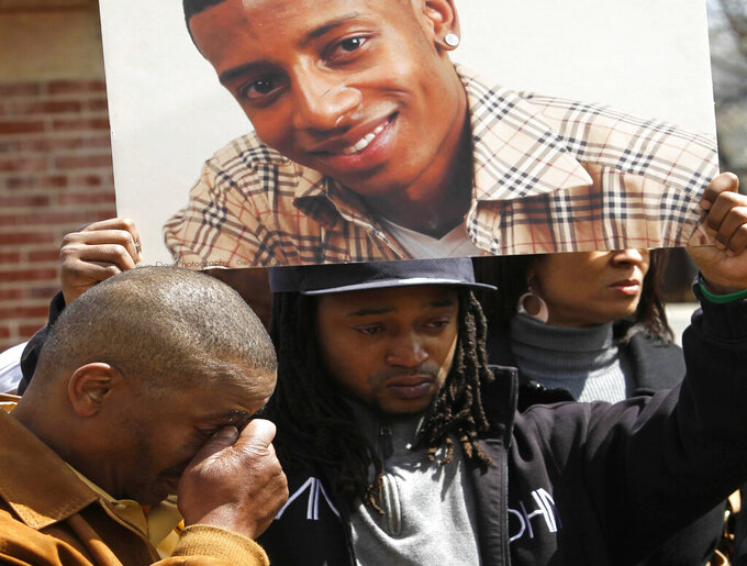 FILE - This file photo from Thursday April 21, 2011, shows a poster photo of Danroy Henry Jr., held up by his uncle Jamele Dozier, while his grandfather Wayne Doozier, left, wipes his eyes during a news conference, in Boston's Roxbury neighborhood. Henry, 20, a college football player, was shot and killed by a police officer in October 2010 in Pleasantville, N.Y. New York's Westchester County District Attorney Mimi Rocah will review Henry's killing and that of a second man, Kenneth Chamberlain, 68, a former Marine who was killed by police in November 2011 in White Plains, N.Y. (AP Photo/Steven Senne, File)