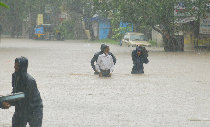 People wade through floodwaters in Kolhapur, in the western Indian state of Maharashtra, Friday, July 23, 2021. Landslides triggered by heavy monsoon rains hit parts of western India, killing more than 30 people and leading to the overnight rescue of more than 1,000 other people trapped by floodwaters, officials said Friday. (AP Photo)
