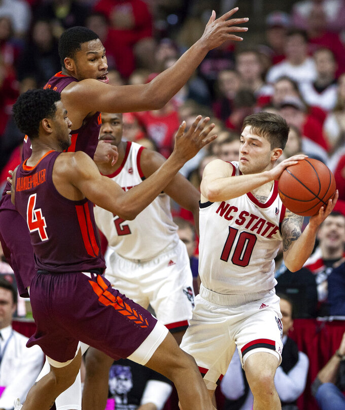 North Carolina State's Braxton Beverly (10) is trapped by Virginia Tech's Nickeil Alexander-Walker (4) and Virginia Tech's Kerry Blackshear Jr., middle, during the second half of an NCAA college basketball game in Raleigh, N.C., Saturday, Feb. 2, 2019. (AP Photo/Ben McKeown)