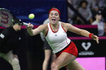 Latvia's Jelena Ostapenko returns a shot from United States' Serena Williams during a Fed Cup qualifying tennis match Friday, Feb. 7, 2020, in Everett, Wash. (AP Photo/Elaine Thompson)