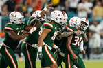 Miami place kicker Andres Borregales (30) is mobbed by teammates after he made a field goal during the final minutes of the second half of an NCAA college football game against Appalachian State, Saturday, Sept. 11, 2021, in Miami Gardens, Fla. (AP Photo/Wilfredo Lee)