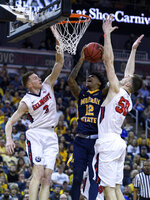 Belmont's Dylan Windler (3) and Belmont's Seth Adelsperger (50) defend against Murray State's Ja Morant (12) as he goes up for a shot during the second half of an NCAA college basketball game for the Ohio Valley Conference men's tournament championship in Evansville, Ind., Saturday, March 9, 2019. (Sam Owens/Evansville Courier & Press via AP)