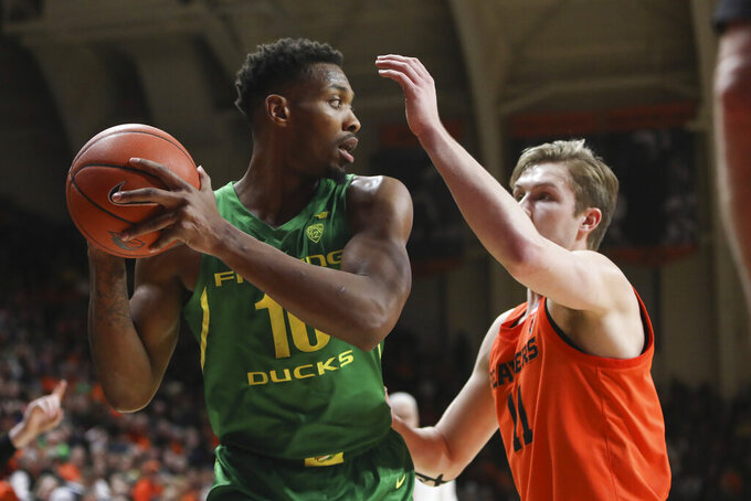 Oregon's Shakur Juiston (10) looks for a way around Oregon State's Zach Reichle (11) during the first half of an NCAA college basketball game in Corvallis, Ore., Saturday, Feb. 8, 2020. (AP Photo/Amanda Loman)