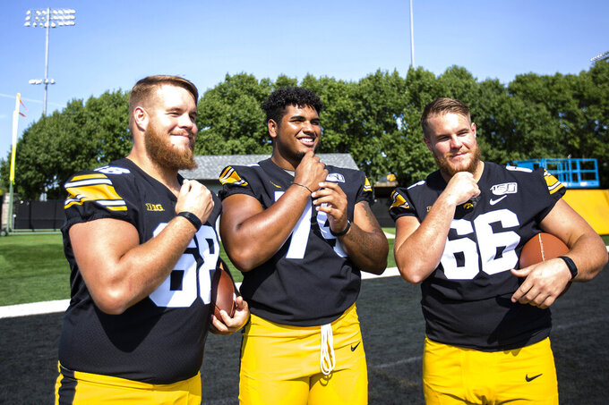 FILE - In this Friday, Aug. 9, 2019, file photo, Iowa offensive linemen Landan Paulsen, from left, Tristan Wirfs and Levi Paulsen show off their beards during Iowa's NCAA college football media day in Iowa City, Iowa. Football players often refer to their teammates as brothers. In the Big Ten, a lot of them truly are. At Iowa, left guard Landan Paulsen and right guard Levi Paulsen will be the team's first twins to start since 1980. (Joseph Cress/Iowa City Press-Citizen via AP, File)