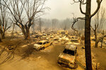 This photo shows cars and homes destroyed by the Dixie Fire line central Greenville on Thursday, Aug. 5, 2021, in Plumas County, Calif. (AP Photo/Noah Berger)