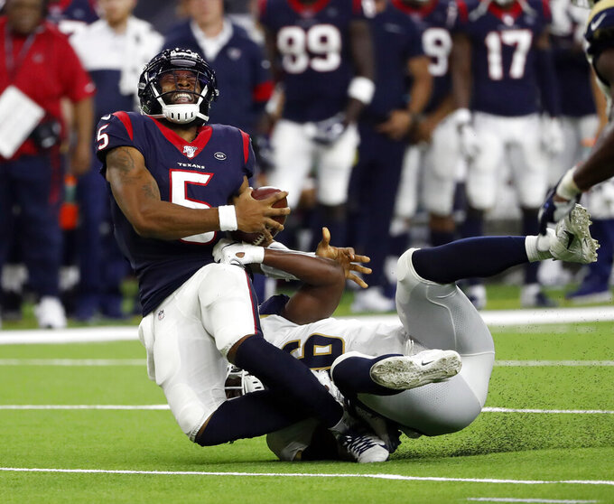Houston Texans quarterback Joe Webb III (5) is tackled by Los Angeles Rams linebacker Landis Durham during the second half of a preseason NFL football game Thursday, Aug. 29, 2019, in Houston. Webb III was injured on the play. (AP Photo/Kevin M. Cox)