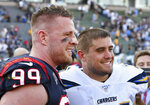 FILE - In this Sept. 22, 2019 file photo, Houston Texans defensive end J.J. Watt (99) stands on the field next to his brother San Diego Chargers fullback Derek Watt (34) after the Texans defeated the Los Angeles Chargers 27 to 20 in an NFL game in Carson, Calif.  The three Watt brothers will share the field for the first time ever on Sunday, Sept. 27, 2020,  when J.J. Watt and the Texans visit T.J., Derek and the Pittsburgh Steelers. (AP Photo/John Cordes, File)
