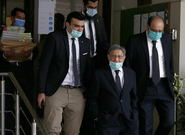 Farooq Naek, center, prosecutor from Sindh provincial government, leaves with his team from the Supreme Court after an appeal hearing of the Daniel Pearl case, in Islamabad, Pakistan, Wednesday, Oct. 7, 2020. Ahmed Omar Saeed Sheikh, who has been on death row over the 2002 killing of U.S. journalist Daniel Pearl, will remain in jail for another three months under a government order, a prosecutor told the country's top court Wednesday, as it took up appeals of Pearl's family and government against acquittal of all accused of murder charges by another court. (AP Photo/Anjum Naveed)