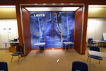 A large Levi's jeans display highlights the center of an empty classroom, built in a former department store, at Downtown Burlington High School, Monday, March 22, 2021, in Burlington, Vt. Students who once shopped at a downtown mall are now attending high school in the mall's former Macy's store, taking escalators to and from classes. The existing Burlington High School was closed last August after PCBs were found in the building. (AP Photo/Charles Krupa)