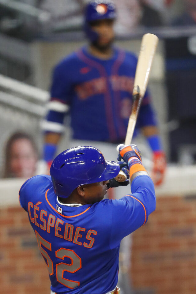 New York Mets' Yoenis Cespedes follows thorough on a two-run double in the fifth inning of a baseball game against the Atlanta Braves Friday, July 31, 2020, in Atlanta. (AP Photo/John Bazemore).