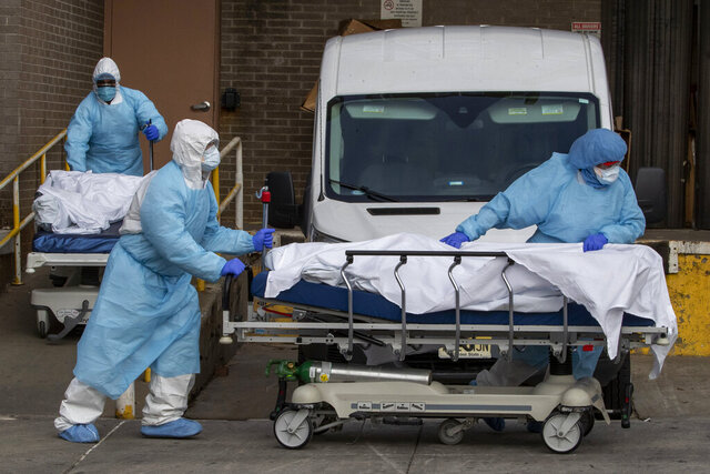 Medical personnel wearing personal protective equipment remove bodies from the Wyckoff Heights Medical Center Thursday, April 2, 2020 in the Brooklyn borough of New York.  As coronavirus hot spots and death tolls flared around the U.S., the nation's biggest city was the hardest hit of the all, with bodies loaded onto refrigerated morgue trucks by gurney and forklift outside overwhelmed hospitals, in full view of passing motorists.   (AP Photo/Mary Altaffer)