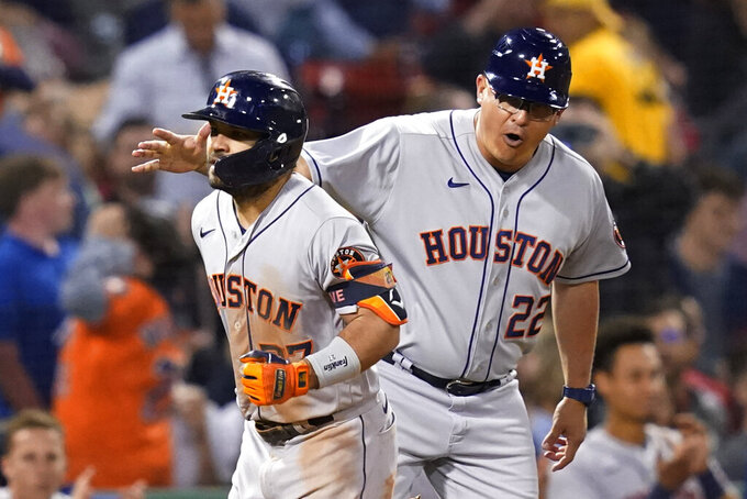 Houston Astros third base coach Omar Lopez (22) celebrates with Jose Altuve, who rounds third after hitting a solo home run during the sixth inning of the team's baseball game against the Boston Red Sox at Fenway Park, Thursday, June 10, 2021, in Boston. (AP Photo/Elise Amendola)