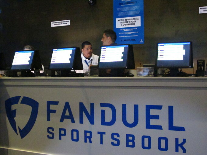 This July 14, 2018 file photo shows workers at the FanDuel sports book at the Meadowlands Racetrack in East Rutherford, N.J., preparing to take bets moments before it opened. FanDuel on Nov. 30 paid off on bets customers made on Alabama to win the national college football championship a month before the game is played. (AP Photo/Wayne Parry, File)