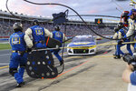The pit crew for Chase Elliott run onto pit road for a pit stop under caution in a NASCAR Cup Series auto race at Charlotte Motor Speedway in Concord, N.C., Sunday, May 30, 2021. (AP Photo/Nell Redmond)