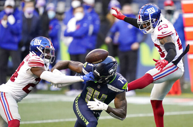 New York Giants cornerback James Bradberry, left, and defensive back Logan Ryan, right, break up a pass intended for Seattle Seahawks wide receiver DK Metcalf (14) during the second half of an NFL football game, Sunday, Dec. 6, 2020, in Seattle. The Giants won 17-12. (AP Photo/Elaine Thompson)