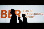 People walk in front of a sign of the new Berlin-Brandenburg-Airport 'Willy Brandt' in inside the Terminal 1, near Berlin in Schoenefeld, Germany, Tuesday, Oct. 27, 2020. After years of delays and massive cost overruns the opening of the German capital's new airport is scheduled for Saturday Oct. 31.(AP Photo/Markus Schreiber)