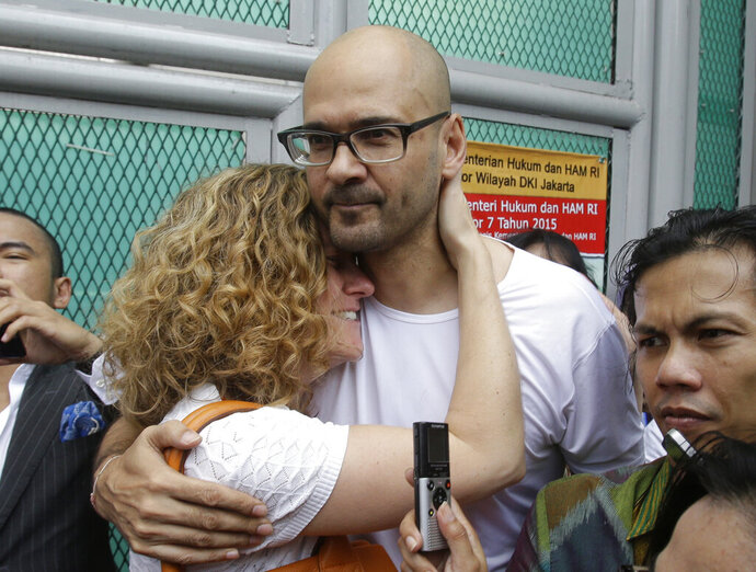 FILE - In this Aug. 14, 2015, file photo, Canadian teacher Neil Bantleman, center right, hugs his wife Tracy, left, after he was released from Cipinang prison in Jakarta, Indonesia. Indonesia has freed the Canadian teacher who maintains he was wrongfully convicted in 2015 of sexually abusing children at an international school in Jakarta. (AP Photo/Achmad Ibrahim. File)