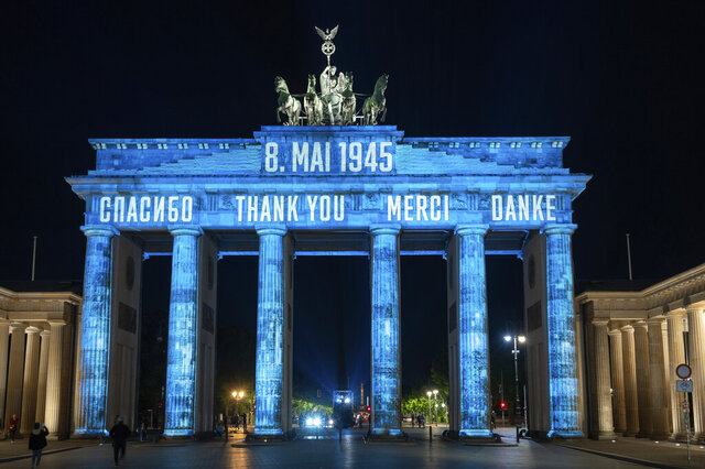 In Russian, from left, English, French and German, the Brandenburg Gate is illuminated with the word