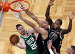 Boston Celtics forward Gordon Hayward (20) goes to the hoop against Milwaukee Bucks center Brook Lopez, middle, and forward Khris Middleton (22) in the fourth quarter of an NBA basketball game, Friday, Dec. 21, 2018, in Boston. (AP Photo/Elise Amendola)