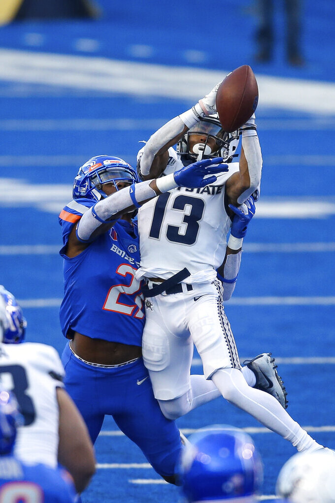 Utah State wide receiver Deven Thompkins (13) attempts to catch the ball against the defense of Boise State safety Tyreque Jones (21) in the first half of an NCAA college football game Saturday, Oct. 24, 2020, in Boise, Idaho. (AP Photo/Steve Conner)
