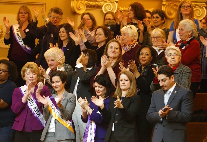 FILE - In this Thursday Feb. 21, 2019 file photo State Senators Janet Howell, D-Fairfax, front left, Jennifer Boysko, D-Fairfax, second from left, and Sen. Barbara Favola, D-Arlington third from left, applaud a speech along with other ERA supporters in the gallery of the the House of Delegates at the Capitol in Richmond, Va., Democrats hoping to seize control of the Virginia Legislature in the 2019 elections say passing the long-stalled Equal Rights Amendment will be a top priority next year.  (AP Photo/Steve Helber)