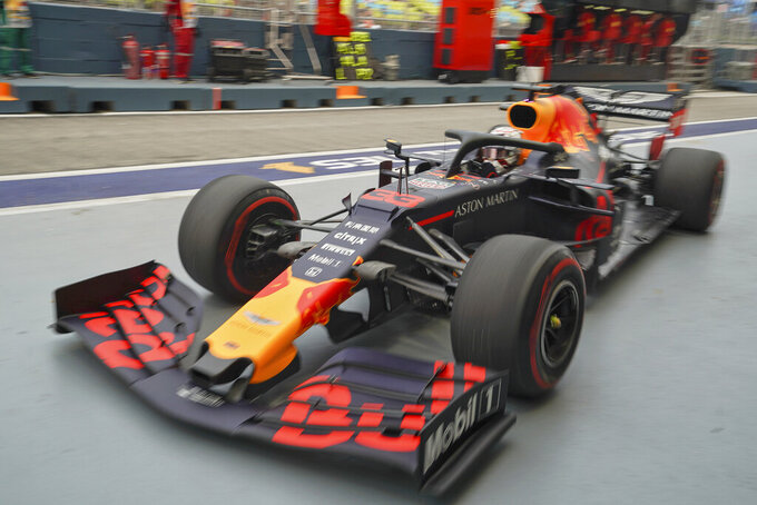Red Bull driver Max Verstappen of the Netherlands returns to his team garage during the first practice session at the Marina Bay City Circuit ahead of the Singapore Formula One Grand Prix in Singapore, Friday, Sept. 20, 2019. (AP Photo/Vincent Thian)