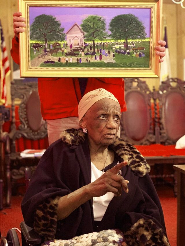 In this photo provided by Bruce Shelton, Painter Helen LaFrance sits under one of her paintings during her 100th birthday party on Saturday, Nov. 2, 2019, in Mayfield, Ky.   LaFrance, a prominent Black Kentucky artist whose painted memories of rural life in Kentucky are featured in U.S. and European museums and hang on the walls of well-known personalities has died on Sunday, Nov. 22, 2020 , according to Brown Funeral Home. (Bruce Shelton via AP)