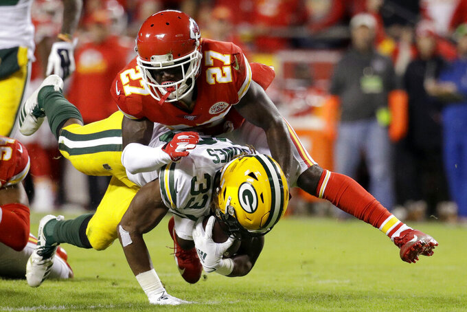 Green Bay Packers running back Aaron Jones (33) is tackled by Kansas City Chiefs cornerback Rashad Fenton (27) during the first half of an NFL football game in Kansas City, Mo., Sunday, Oct. 27, 2019. (AP Photo/Charlie Riedel)