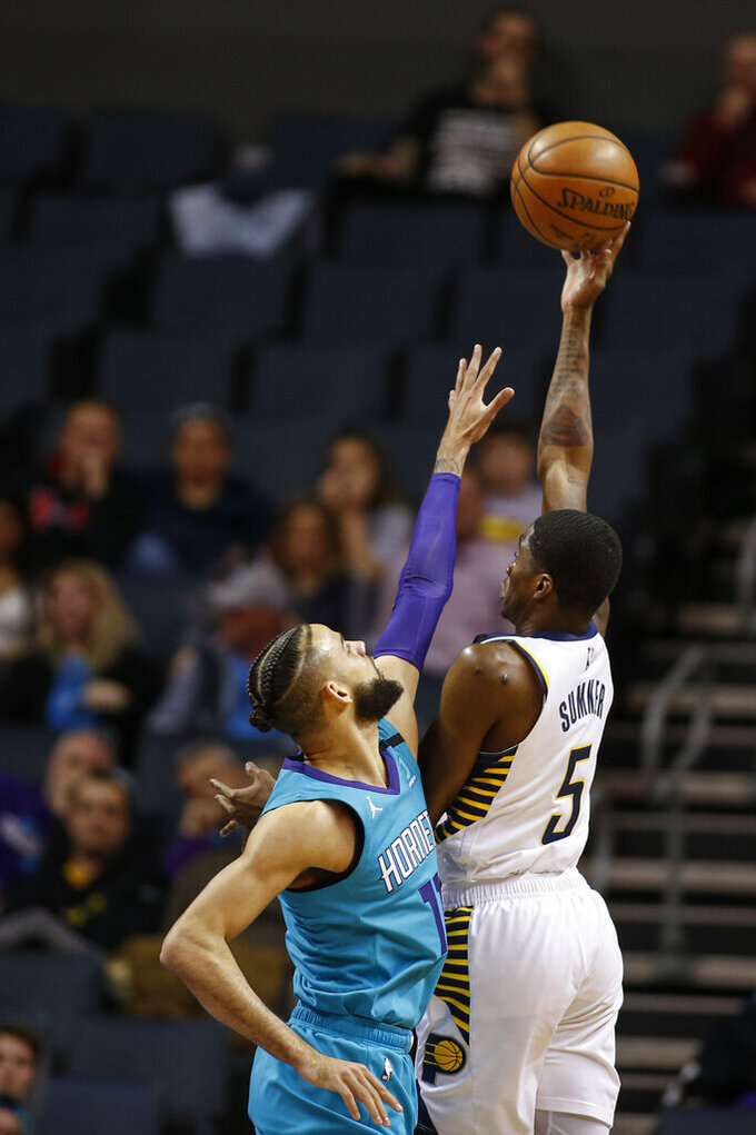 Indiana Pacers guard Edmond Sumner, right, shoots over Charlotte Hornets forward Cody Martin in the first half of an NBA basketball game in Charlotte, N.C., Monday, Jan. 6, 2020. (AP Photo/Nell Redmond)