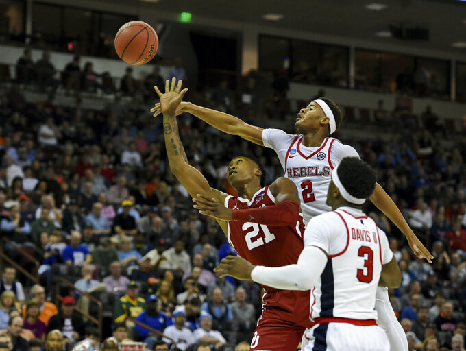Mississippi's Devontae Shuler (2) knocks the ball away from Oklahoma's Kristian Doolittle (21) while Mississippi's Terence Davis (3) watches during a first round men's college basketball game in the NCAA Tournament in Columbia, S.C. Friday, March 22, 2019. (AP Photo/Richard Shiro)