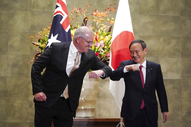 Australian Prime Minister Scott Morrison, left, and Japanese Prime Minister Yoshihide Suga bump elbows to greet prior to the official welcome ceremony at Suga's official residence in Tokyo Tuesday, Nov. 17, 2020. Morrison is in Japan to hold talks with Suga to bolster defense ties between the two U.S. allies to counter China's growing assertiveness in the Asia-Pacific region. (AP Photo/Eugene Hoshiko, Pool)