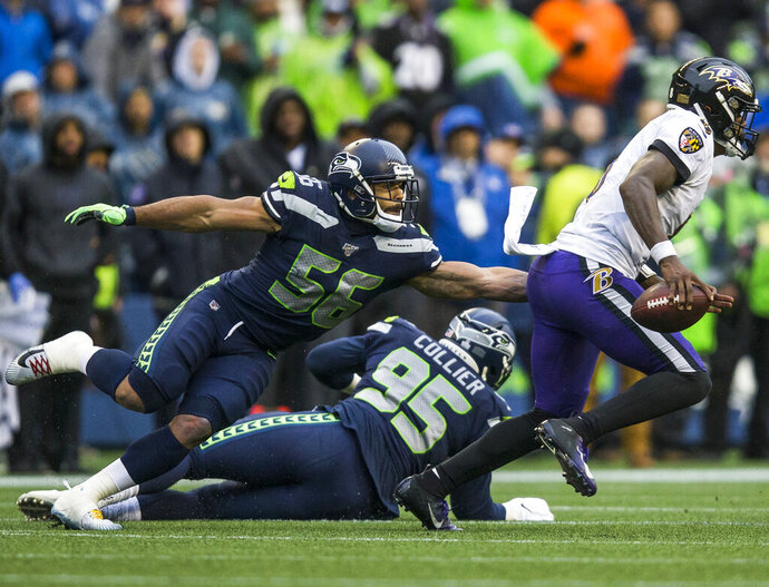 Seattle Seahawks' Mychal Kendricks (56) reaches to try and tackle Baltimore Ravens' Lamar Jackson, right, during an NFL football game Sunday, Oct. 20, 2019, in Seattle, Wash. (Olivia Vanni/The Herald via AP)