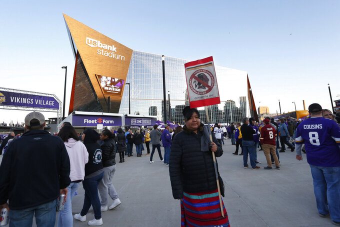 Native American leaders protest outside U.S. Bank Stadium before an NFL football game between the Minnesota Vikings and the Washington Redskins, Thursday, Oct. 24, 2019, in Minneapolis. The group was protesting to urge the visiting Washington team to retire the Redskins team name and mascot. (AP Photo/Bruce Kluckhohn)