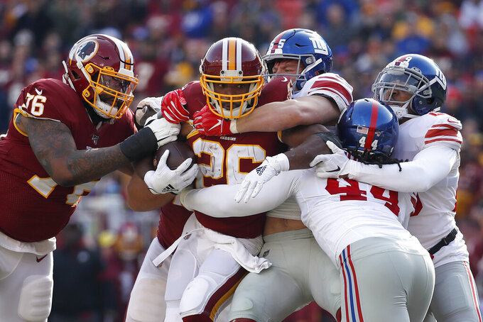 Washington Redskins running back Adrian Peterson, second from left, is wrapped up by, New York Giants, from left, outside linebacker David Mayo, linebacker Markus Golden and outside linebacker Deone Bucannon during the first half of an NFL football game, Sunday, Dec. 22, 2019, in Landover, Md. Redskins offensive tackle Morgan Moses, far left, tries to help on the play. (AP Photo/Alex Brandon)